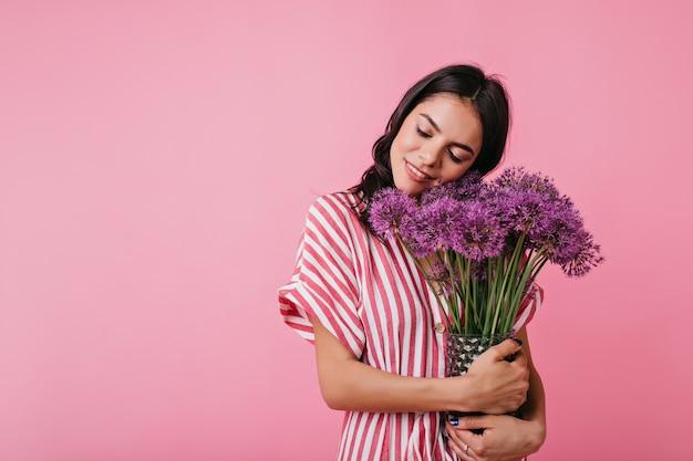 Charmante italiaanse vrouw in een goed humeur poseert met paarse bloemen.