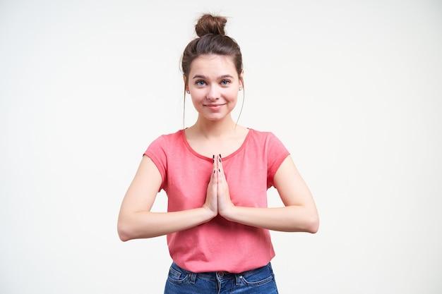 Charmante jonge aantrekkelijke blauwogige brunette dame met broodje kapsel verhogen handen in gebed gebaar en glimlachend aangenaam naar camera terwijl poseren op witte achtergrond