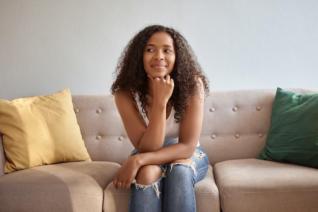 Charmante jonge afro-amerikaanse vrouw met losse krullend haar zittend op de bank thuis trendy gescheurde spijkerbroek en witte tank top dragen, wegkijken met peinzende uitdrukking, denkend over plannen in het weekend