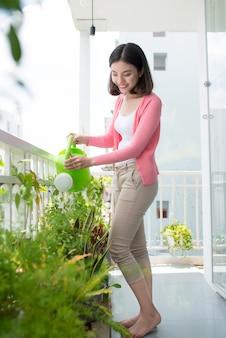 Charmante jonge aziatische vrouw die plant in container op balkontuin water geeft
