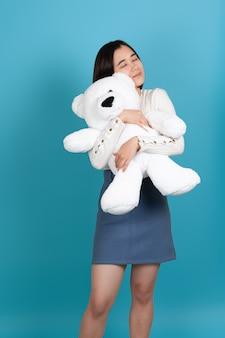 Charmante jonge aziatische vrouw met haar ogen dicht knuffelt stevig een grote witte teddybeer