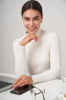 Charmante jonge blauwogige brunette vrolijke vrouw haar kin leunend op opgeheven hand en gelukkig kijken naar camera, in een leuke bui tijdens het werken op kantoor