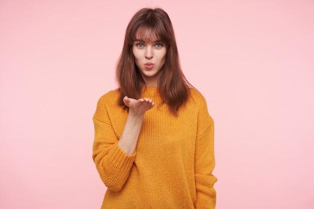 Charmante jonge blauwogige brunette vrouw vouwt haar lippen in luchtkus en blaast erop, haar handpalm omhoog houdend terwijl ze over de roze muur staat