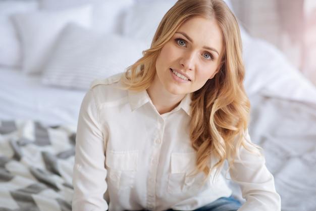 Charmante jonge blonde vrouw zittend op het bed, glimlachend en kijkend naar de voorkant met kussens op de achtergrond.