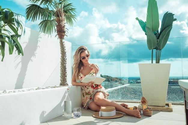 Charmante jonge blonde zit op het balkon en leest een boek.