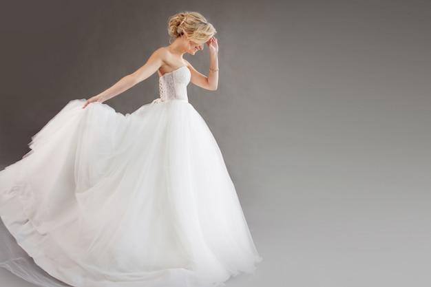Charmante jonge bruid in luxe trouwjurk. mooi meisje op witte, grijze achtergrond, plaats voor uw tekst aan de rechterkant