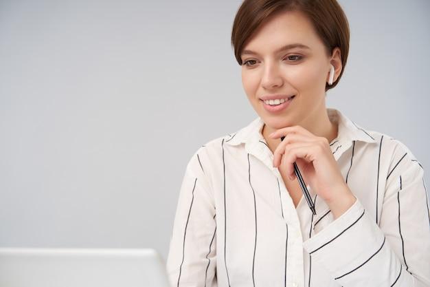 Charmante jonge bruinharige dame met natuurlijke make-up zachtjes haar kin aan te raken met opgeheven hand en vooruit te kijken met een aangename glimlach, geïsoleerd op wit