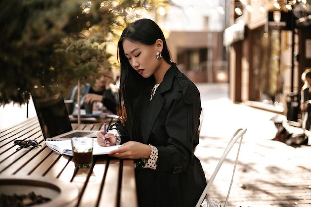 Charmante jonge brunette dame in zwarte trenchcoat maakt aantekeningen in notitieboekje en werkt in laptop