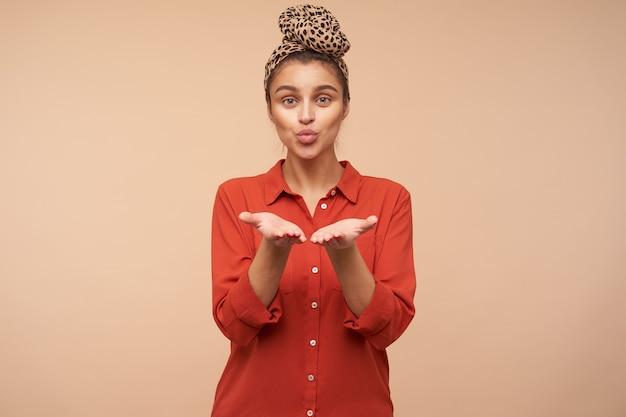 Charmante jonge brunette met groene ogen met hoofdband die haar handpalmen omhoog houdt en de lippen tuit terwijl ze een luchtkus aan de voorkant stuurt, poseren over beige muur