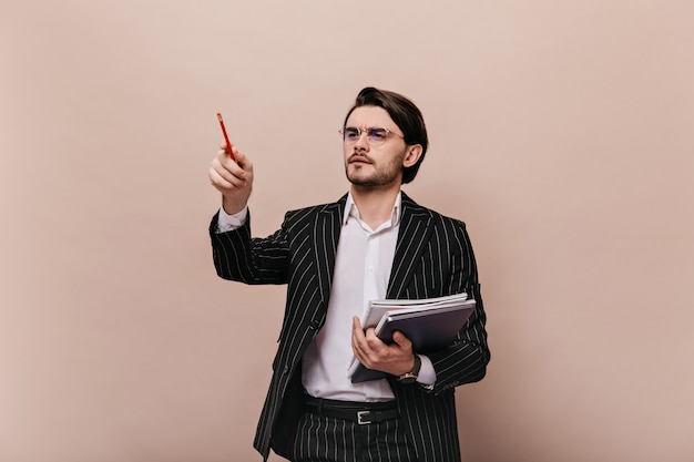 Charmante jonge brunette met wit overhemd, gestreept pak, bril, papieren in de ene hand en wijzend op vrije ruimte met potlood point