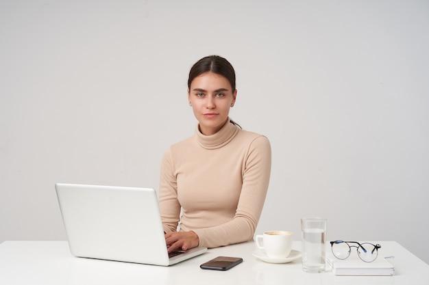 Charmante jonge brunette zakenvrouw werken in een modern kantoor met haar laptop, handen op het toetsenbord houden terwijl ze positief naar de camera kijkt, geïsoleerd over een witte muur