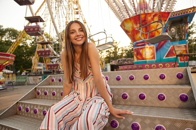 Charmante jonge dame in romantische zomerjurk zittend op pretpark decoraties, in een goede bui, kijken met een brede oprechte glimlach