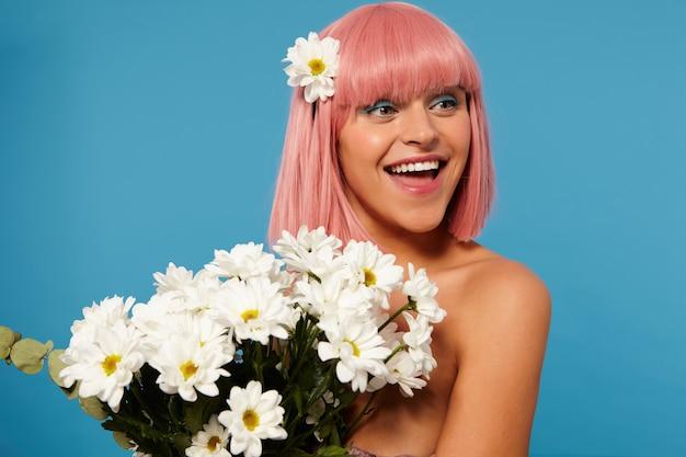 Charmante jonge dame met kort roze haar die positief opzij kijkt en breed glimlacht, terwijl ze staande een armvol bloemen in haar handen houdt