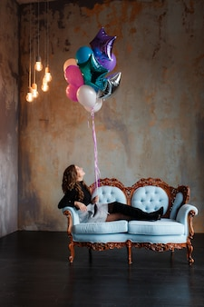 Charmante jonge donkerbruine vrouw die een grote bundel van heliumballons houdt liggend op bank