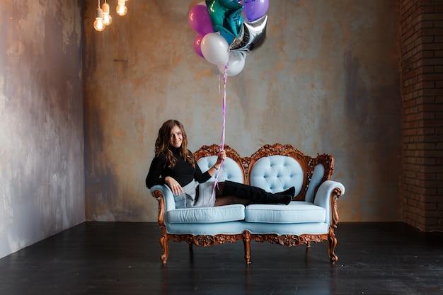 Charmante jonge donkerbruine vrouw die een grote bundel van heliumballons houdt
