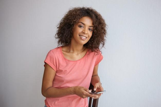 Charmante jonge donkere vrouw met krullend haar op zoek vrolijk, leunend op een stoel en mobiele telefoon in handen houden, poseren