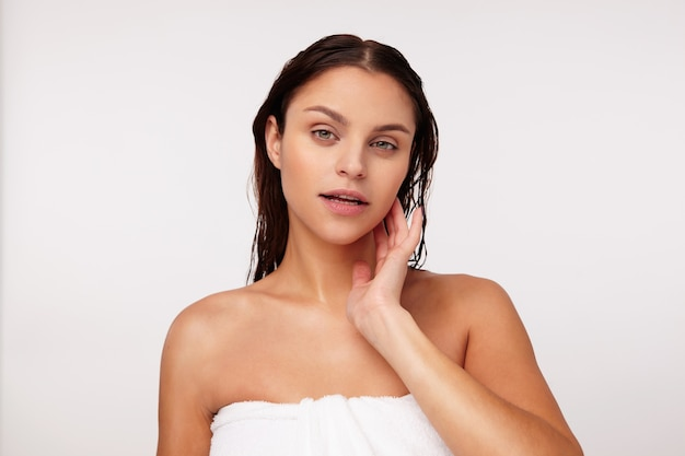 Charmante jonge donkerharige dame met groene ogen zonder make-up die zacht haar wang aanraakt en kalm kijkt, poseren na het douchen