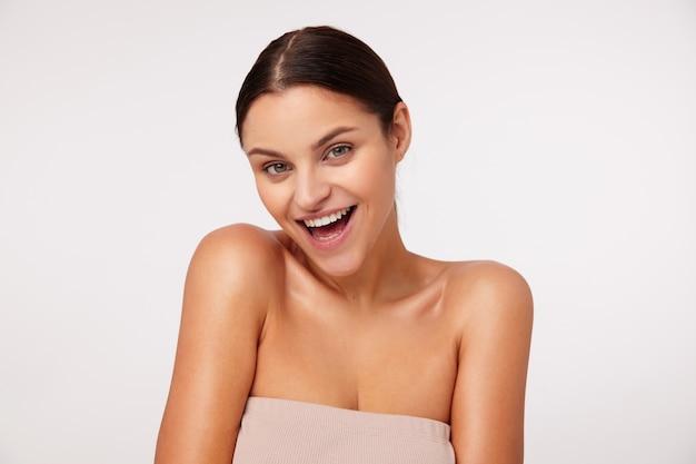 Charmante jonge donkerharige vrouw met groene ogen en natuurlijke make-up die er vrolijk uitziet en wijd lacht, gekleed in een beige top met geopende schouders