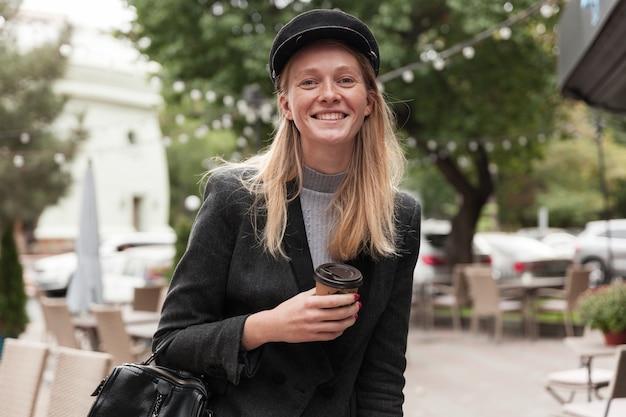 Charmante jonge gelukkig blonde langharige dame in zwarte hoed en elegante blazer poseren met papieren beker in opgeheven hand, breed glimlachend tijdens het kijken
