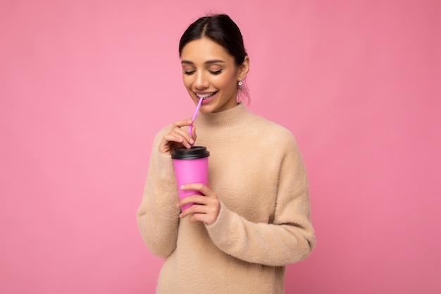 Charmante jonge gelukkig lachende brunette vrouw, gekleed in stijlvolle kleding geïsoleerd op kleurrijke achtergrond