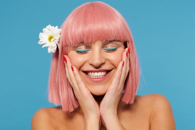 Charmante jonge gelukkig roze harige vrouw met rode manicure die haar gezicht met opgeheven handpalmen vasthoudt terwijl ze oprecht lacht met gesloten ogen, geïsoleerd