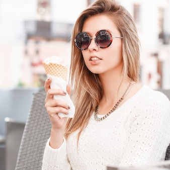 Charmante jonge hipster blonde vrouw in stijlvolle zonnebril in een vintage gebreide trui met zoet ijs zit in een café op een warme lentedag. leuk meisje dat een heerlijk roomijs eet.