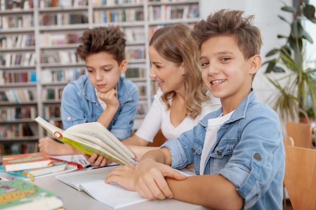 Charmante jonge jongen glimlachen, zijn tweelingbroer en moeder die een boek lezen