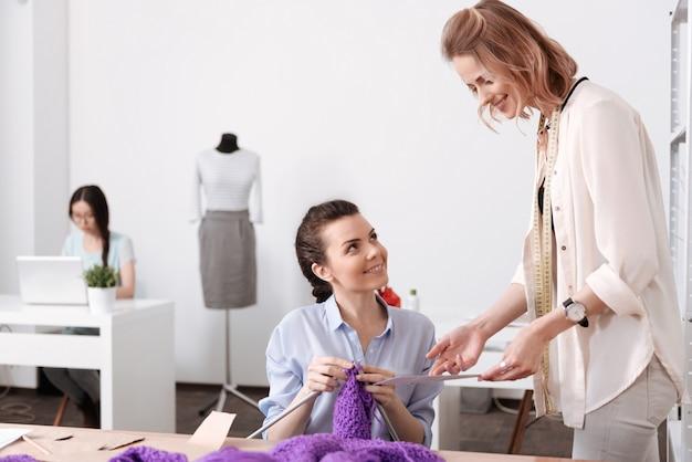 Charmante jonge kleermaker toont een kleurenschema aan haar collega, vraagt om haar mening erover terwijl de collega breit en haar glimlachend aankijkt