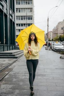 Charmante jonge krullende vrouw gebruik gele paraplu in de straat van megapolis stad in regenachtige dag