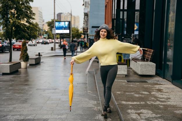 Charmante jonge krullende vrouw met gele paraplu aan de straat van megapolis stad in regenachtige dag