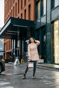 Charmante jonge krullende vrouw met mooie glimlach die de straat van de stad op regenachtige dag loopt