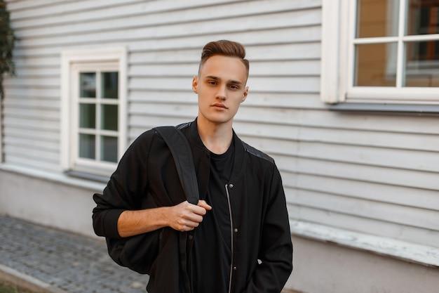 Charmante jonge man in een stijlvolle zomerjas met een zwarte rugzak met een stijlvol kapsel in een t-shirt poseren in de buurt van een houten huis op een zomerdag