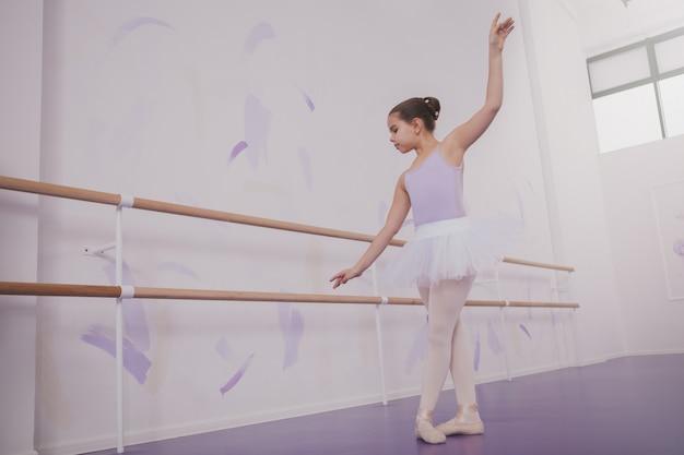 Charmante jonge meisjesballerina die op dansschool uitoefenen