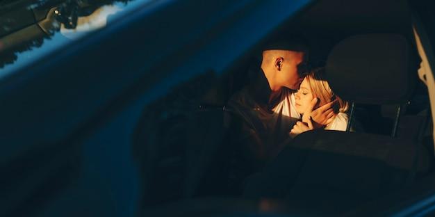 Charmante jonge paar omarmen en kussen in de auto tijdens het reizen in hun vakantietijd.