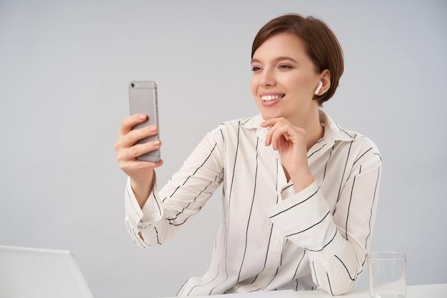 Charmante jonge positieve bruinharige vrouw met natuurlijke make-up zachtjes haar kin aan te raken met opgeheven hand van haar telefoon en aangenaam glimlachend, geïsoleerd op wit