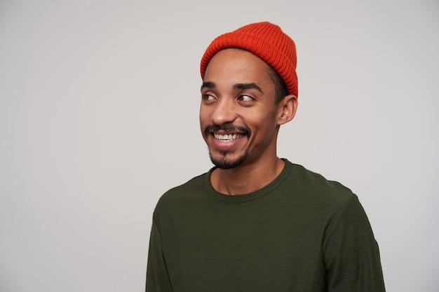 Charmante jonge positieve donkerharige bebaarde man met donkere huid kijkt gelukkig opzij met een brede oprechte glimlach, in goed humeur terwijl hij op wit staat