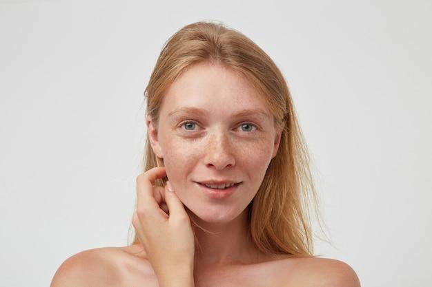 Charmante jonge roodharige vrouw met groene ogen en casual kapsel die zachtjes haar gezicht aanraakt met opgeheven hand en positief kijkt met een aangename glimlach, geïsoleerd over witte muur