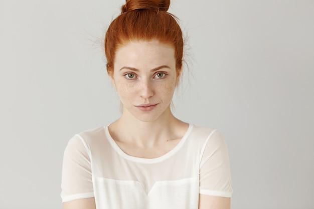 Charmante jonge roodharige vrouw met haarbroodje dat zich tegen witte blinde muur bevindt
