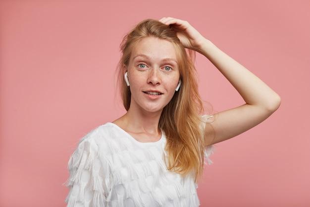 Charmante jonge verrast roodharige vrouw met groen-grijze ogen die haar haar vasthoudt met opgeheven hand en positief naar de camera kijkt, staande tegen een roze achtergrond
