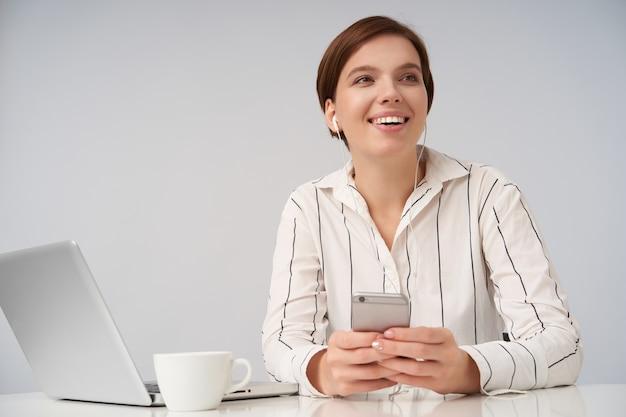 Charmante jonge vrolijke kortharige brunette dame met natuurlijke make-up, luisteren naar muziek met koptelefoon en smartphone terwijl poseren op wit in gestreept overhemd