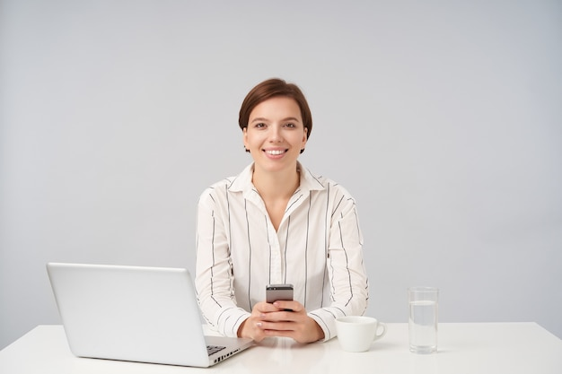 Charmante jonge vrolijke kortharige brunette vrouw toont haar witte perfecte tanden terwijl ze aangenaam lacht, zittend op wit met mobiele telefoon in haar handen