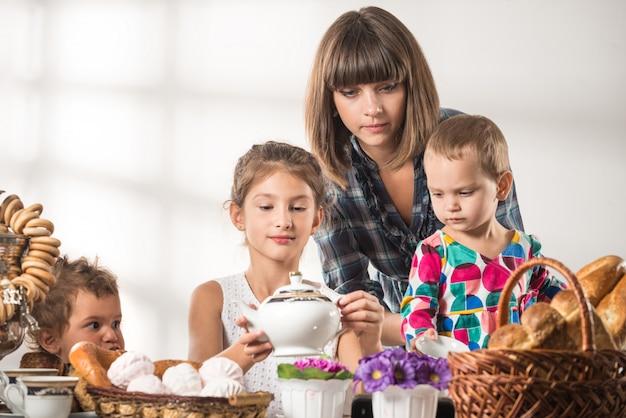 Charmante jonge vrouw dekt de tafel voor kinderen