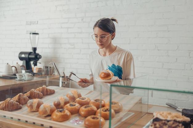 Charmante jonge vrouw die bij de vitrine staat met gebak in café