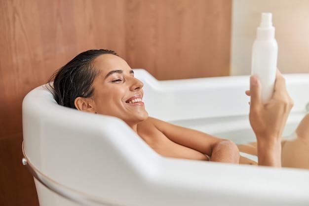 Charmante jonge vrouw die een fles lotion vasthoudt terwijl ze in bad gaat