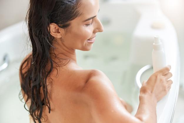 Charmante jonge vrouw die een fles lotion vasthoudt terwijl ze ontspant in badkuip