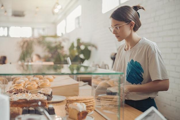 Charmante jonge vrouw die in de bakkerij werkt