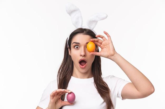 Charmante jonge vrouw die in konijnenoren gekleurd ei houdt