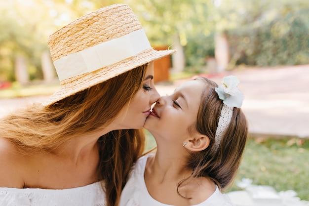 Charmante jonge vrouw die met lange zwarte wimpers haar glimlachende dochter met liefde kust. close-up portret van mooie moeder en schattige langharige vrouwelijke jongen met lint.