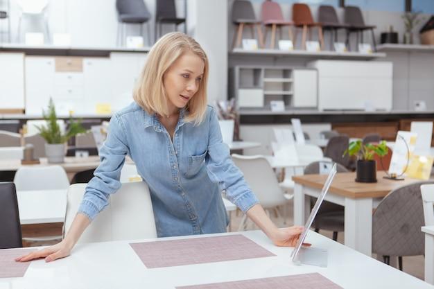 Charmante jonge vrouw die meubilair kiest om voor haar nieuw huis te kopen