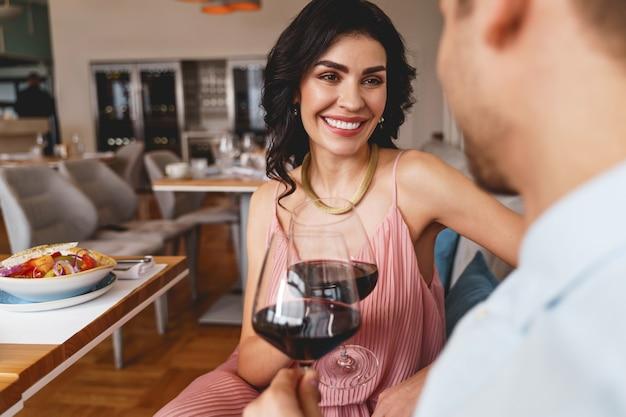 Charmante jonge vrouw die naar de man kijkt en glimlacht terwijl ze glazen wijn rammelt